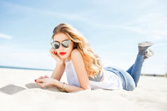 Attractive girl in sunglasses posing lying on the sea beach on a Stock Photography