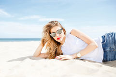 Attractive girl in sunglasses posing lying on the sea beach on a Royalty Free Stock Photo