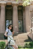 Attractive girl in sunglasses sitting on bike and using smartphone near beautiful building with columns. And stairs royalty free stock image