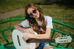 Attractive girl in sunglasses sitting with a guitar royalty free stock photo