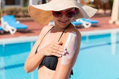 Attractive girl in sunhat applying sunscreen on shoulder by the pool. Sun Protection Factor in vacation, concept.  royalty free stock photo