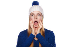 Attractive girl in sweater and winter cap expresses surprise Royalty Free Stock Image