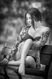 Attractive girl in swimsuit sitting relaxed on a bench. Fashionable female model with romantic look posing in park. Beautiful girl Royalty Free Stock Image