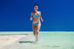 Attractive girl in swimwear running along the tropical beach royalty free stock photo