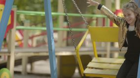 Attractive girl swinging on the swing on the playground. Happy child playing alone outdoors. Carefree childhood. Attractive positive teenage girl swinging on the stock video footage