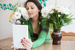 Attractive girl with a tablet. Young attractive girl at home, sitting at the table with a tablet, and reading something in internet. There is a beautiful flowers Stock Image