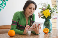 Attractive girl with a tablet. Young attractive girl at home, sitting at the table with a tablet. On the table in the vase are beautiful flowers and oranges. The Royalty Free Stock Photo