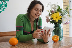 Attractive girl with a tablet. Young attractive girl at home, sitting at the table with a tablet. On the table in the vase are beautiful flowers and oranges. The Stock Image