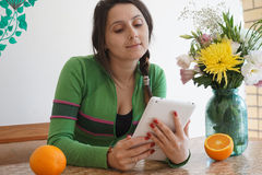 Attractive girl with a tablet. Young attractive girl at home, sitting at the table with a tablet. On the table in the vase are beautiful flowers and oranges. The Stock Photography
