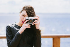 Attractive girl takes pictures with an old camera Stock Images