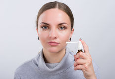 Attractive girl taking a medicine with spray inside the throat on light background Stock Photography