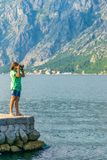 An attractive girl is taking pictures. Of the seascape Stock Photos