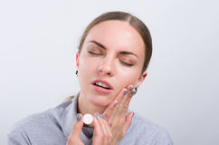 Attractive girl taking a pill on light background Royalty Free Stock Images