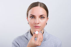 Attractive girl taking a pill on light background Royalty Free Stock Photos