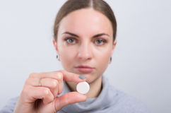 Attractive girl taking a pill on light background stock images