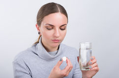 Attractive girl taking a pill with water on light background Stock Photos