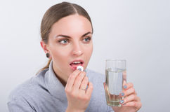 Attractive girl taking a pill with water on light background Royalty Free Stock Image