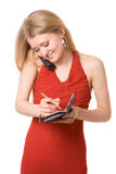 Attractive girl talk at phone and write to noteboo Royalty Free Stock Image