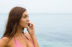 Attractive girl talking on a mobile on the beach. Royalty Free Stock Photo