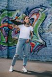 Attractive girl with tattoos holding skateboard over shoulder near wall. With graffiti royalty free stock photography