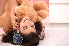 Attractive girl with teddy bear on phone. Attractive girl laying on floor at home, hugging huge teddy bear, chatting on mobile Royalty Free Stock Images