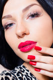 Attractive girl, tempting brunette beuatiful young woman with blue eyes, long lashes, red lipstick & nails looking at camera Stock Images