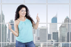 Attractive girl with thumbs up in office Stock Image
