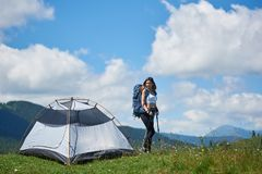 Woman tourist near camping in the mountains with backpack and trekking sticks in the morning. Attractive girl tourist with backpack and trekking sticks near tent Royalty Free Stock Images