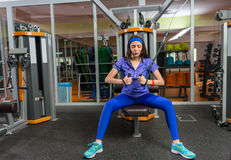 Attractive girl training on row machine in gym. Room in fitness center Stock Photos