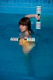 Attractive girl trains in aqua aerobics Royalty Free Stock Photography