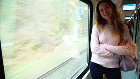 Attractive girl traveling by train and happy about new adventures, smiling and showing gesture to  camera in  transport. Stunning young woman looks and poses in stock footage