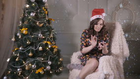 Attractive girl use smartphone near Christmas tree during New Year celebration. stock footage