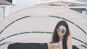 Attractive girl uses digital tablet resting on beach lounge in 4K stock video