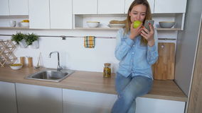 Attractive girl uses smart phone and eats apple, sitting on kitchen surface near sink in kitchen during day. Young woman flips through newsfeed or sits on stock footage