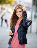 Attractive girl using her smart phone Stock Photography
