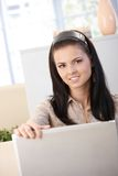 Attractive girl using laptop smiling Stock Image