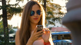 Attractive girl using mobile phone in a city. Smiling reading the messages on the smartphone screen stock video footage