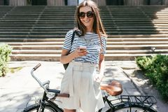 Attractive girl using smartphone and smiling at camera while standing with bicycle. On street stock photo