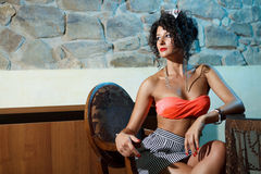 Attractive girl waiting. At table in restaurant, wearing orange bra, short dress Royalty Free Stock Images