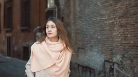 Attractive girl walking alone in the old town. Brunette woman going through the street. Female have vacation in Europe. Attractive girl with pink scarf walking stock footage