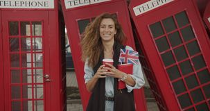 Attractive girl walking on a background of red British phones. Drinks coffee and sightseeing. stock video footage