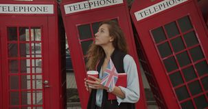 Attractive girl walking on a background of red British phones. Drinks coffee and sightseeing. stock video