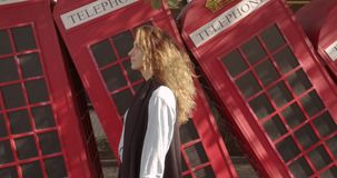 Attractive girl walking on a background of red British phones. Travel, tourist places concept. stock footage