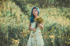 Attractive girl walking on flower field Stock Photo