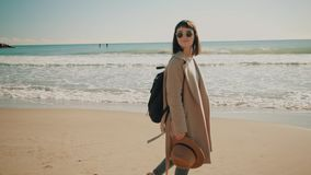 Attractive girl walks near shore line in small mediterranean town. Camera follows beautiful smiling girl in wool coat and with black backpack escaped from city stock video footage