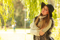 Attractive girl warm herself. Autumnal female fashion. Pretty young woman wearing stylish sweater waistcoat and hat warm herself outdoor. Beauty fashionable Stock Photos