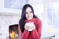 Attractive girl warming at fireplace hold coffee Stock Photography