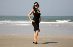 Attractive girl wearing black dress on a beach Royalty Free Stock Photography