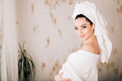 Attractive girl wearing white bathrobe and towel on head in bathroom. Spa Woman. Portrait of tender caucasian young woman with clean skin, white towel on her royalty free stock photography