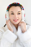 Attractive girl wearing a white coat and ear muffs looking away. Stock Photography